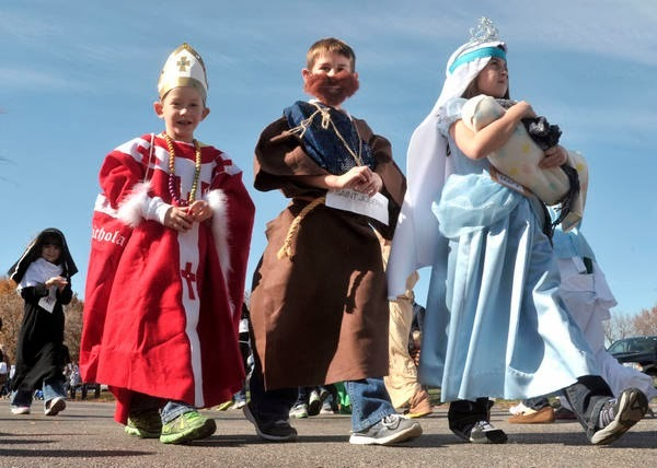 John Dixon/The News-GazetteStand Alone - From left, St. Matthew school 1st grade students Grant Evangelisti(cq), 6 (St. Nicholas), Alex Dobbins, 6 (St. Joseph) and Reagan Chladny(cq), 6 (Holy Mother Mary) parade past parents, family and other students in the school's annual All Saints Day parade in Champaign on Friday Oct. 26, 2012.